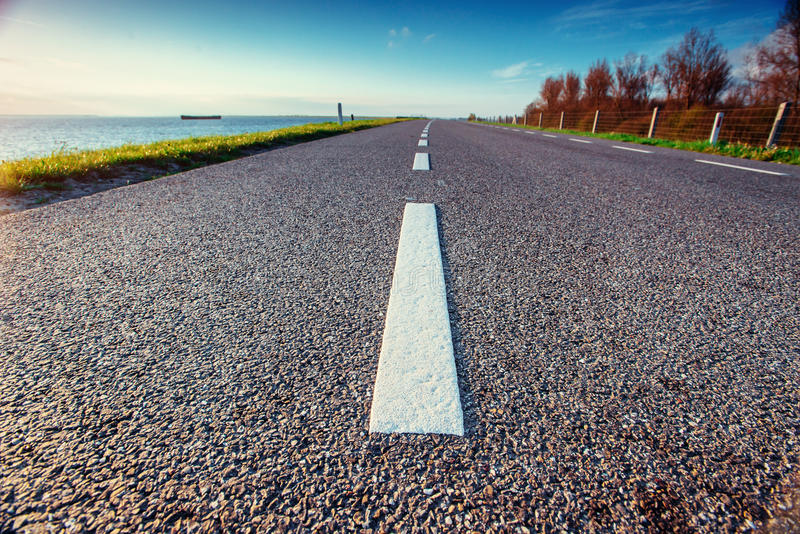 Asphalt road along the sea in a fantastic summer day. In the sun royalty free stock images