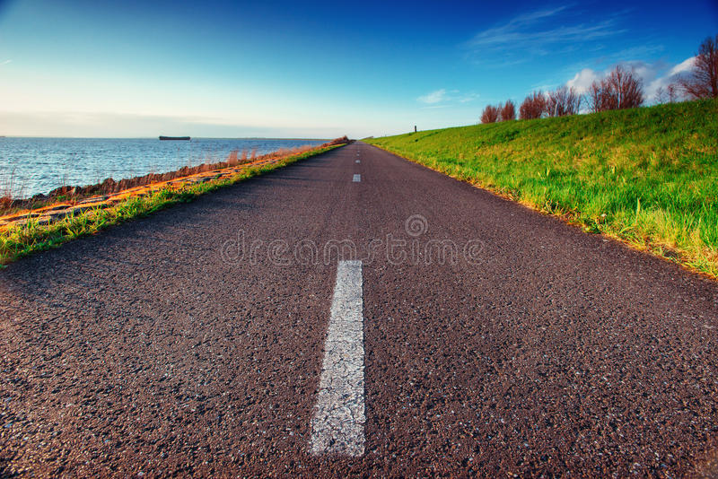 Asphalt road along the sea in a fantastic summer day. In the sun royalty free stock photos