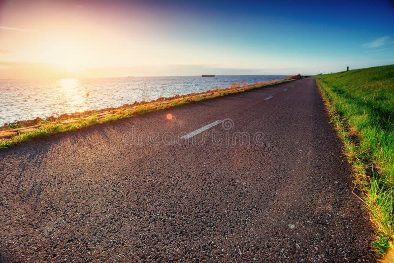 Asphalt road along the sea at sunset.  royalty free stock photography