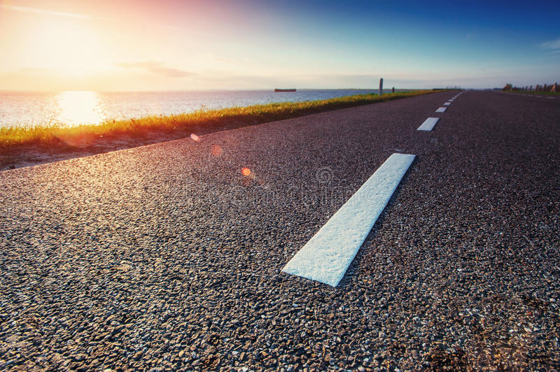 Asphalt road along the sea at sunset.  royalty free stock photo