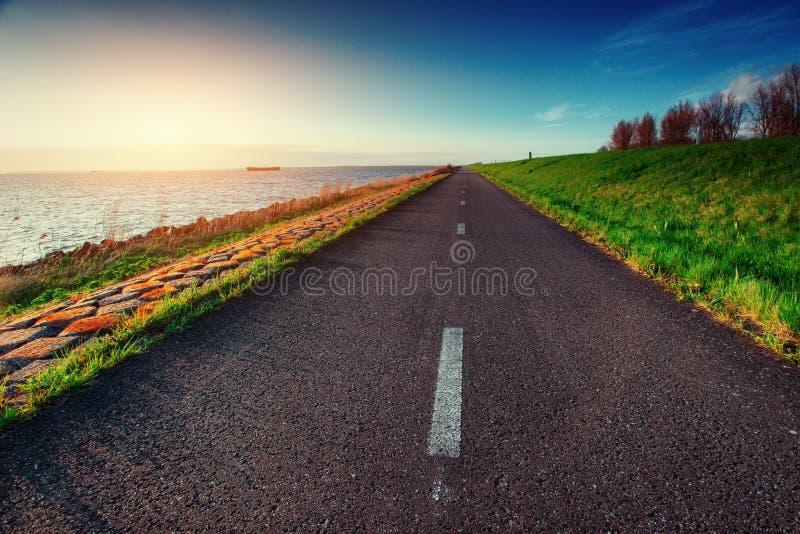Asphalt road along the sea at sunset.  royalty free stock image