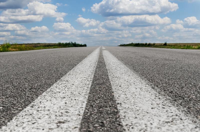 Asphalt road closeup with two white lines in center stock image