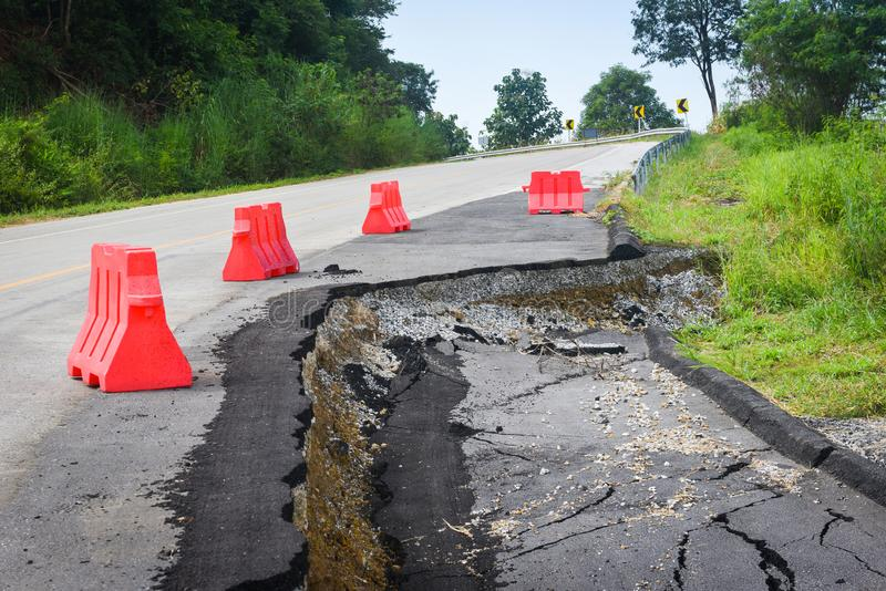 Asphalt road collapsed and cracks in the roadside - Road landslide subside with plastic barriers on uphill. Asphalt road collapsed and cracks in the roadside / royalty free stock photos