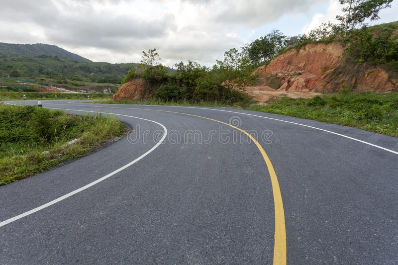 Asphalt road curve on the mountain in bad weather day royalty free stock photos