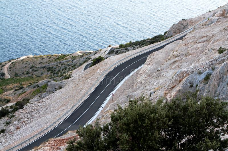 Asphalt road curving trough mountain stock photos