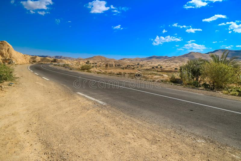 Asphalt road in a desert. With blue sky on the background royalty free stock image