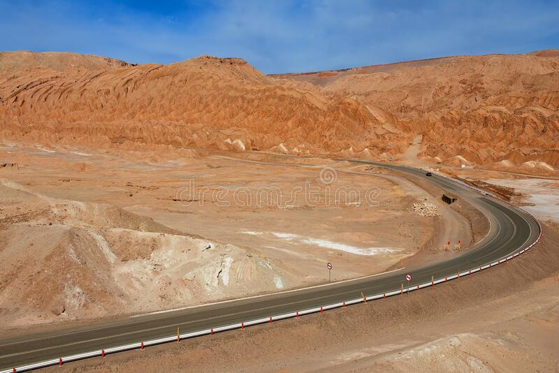 Asphalt road with extreme landscape next to the Moon valley in Atacama desert at San Pedro de Atacama, Chile. royalty free stock photography