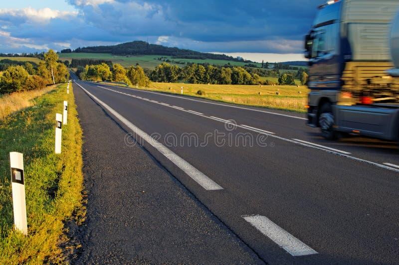 Asphalt road through the fields towards the horizon