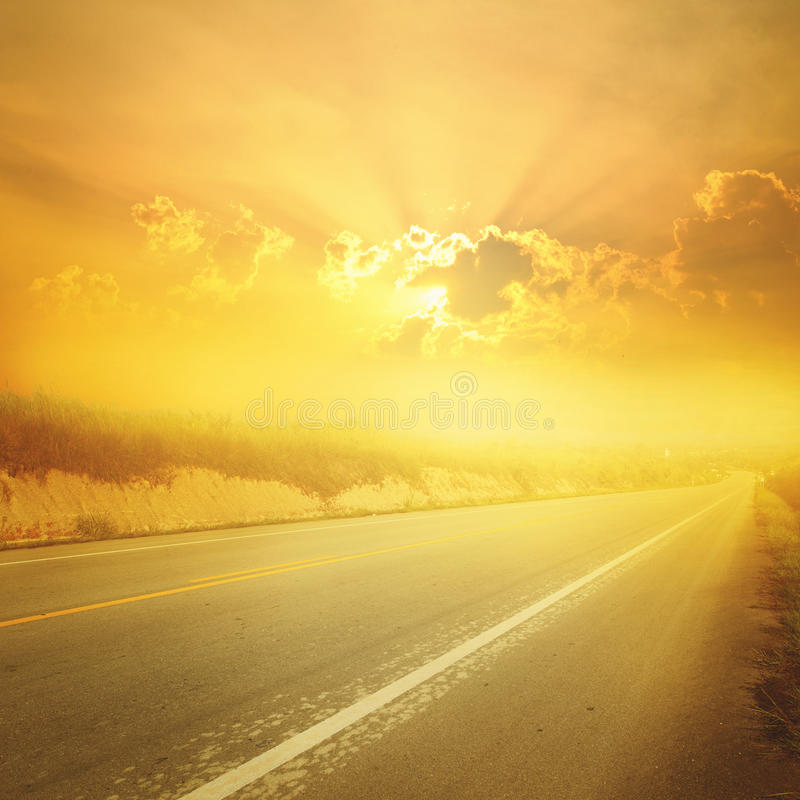 Asphalt road in forrest and sunset for transportation stock photography