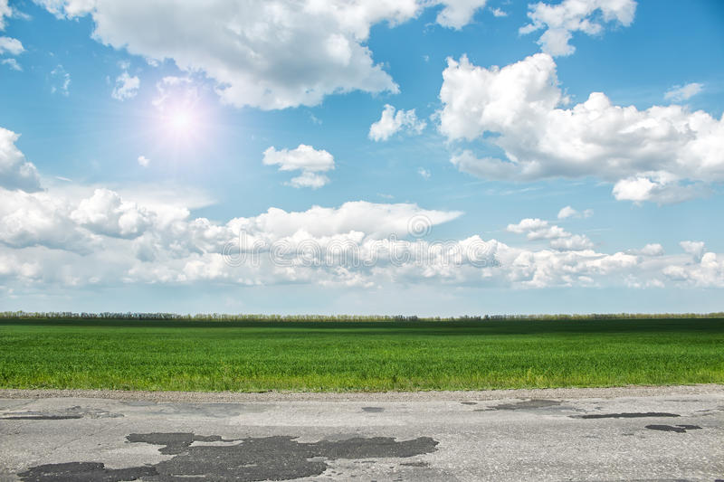 Asphalt road and green field at sunny summer day royalty free stock images