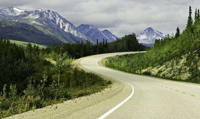 Asphalt road in high mountains of Alaska stock photos