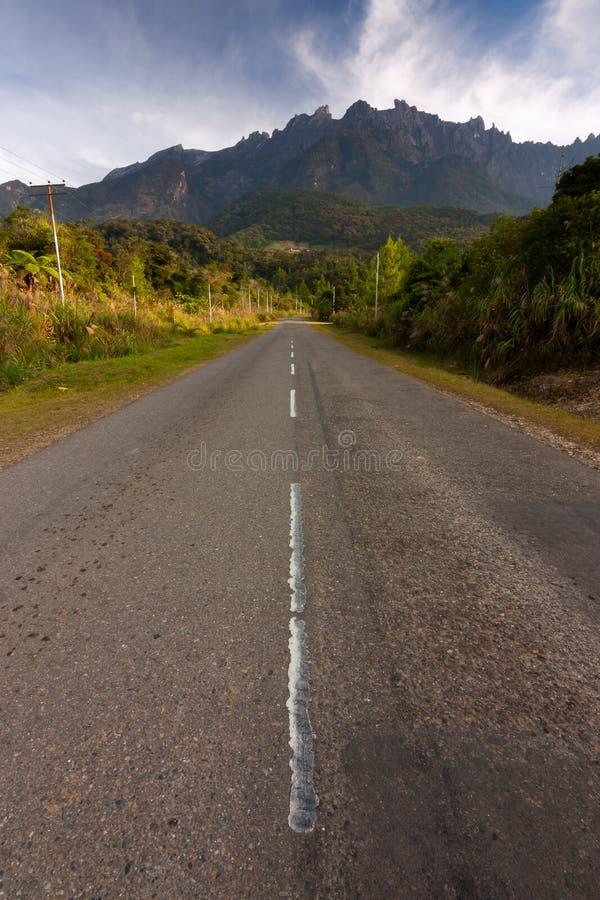 Asphalt road leading to Mount Kinabalu royalty free stock photography