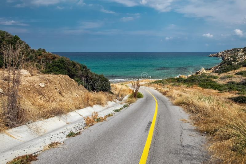 The asphalt road leads to a hidden beach of Cyprus island. Dead end at the sea coast. royalty free stock images