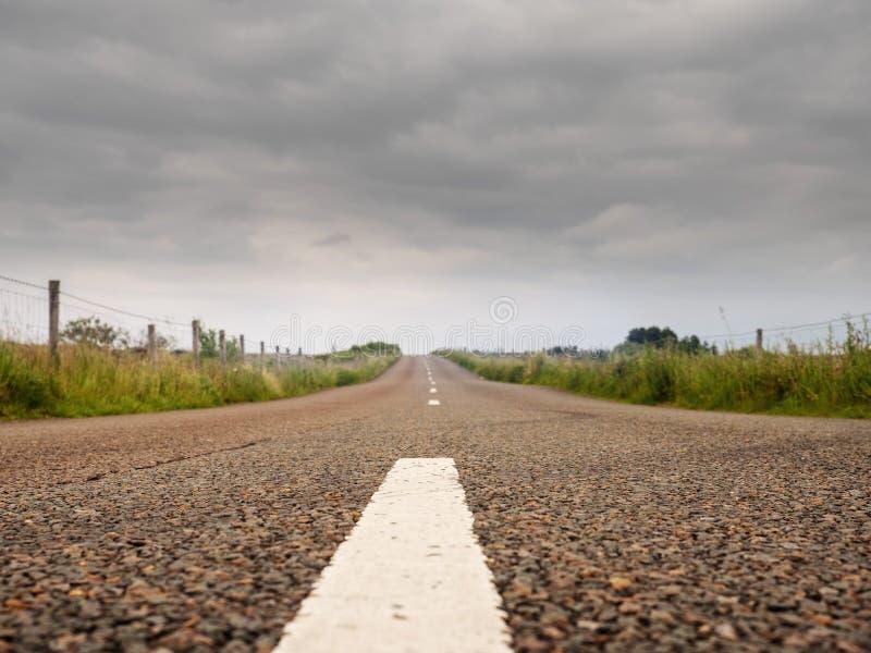 Asphalt road, low angle, Cloudy sky, Concept driving, way to your destination. Asphalt road, low angle, Cloudy moody sky, Concept driving, way to your stock image
