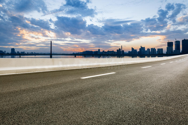 Asphalt road and modern city skyline at sunset royalty free stock image