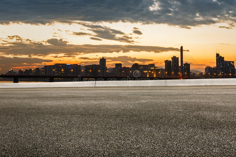 Asphalt road and modern city skyline at sunset. The beauty of the Asphalt road and modern city skyline at sunset royalty free stock photography