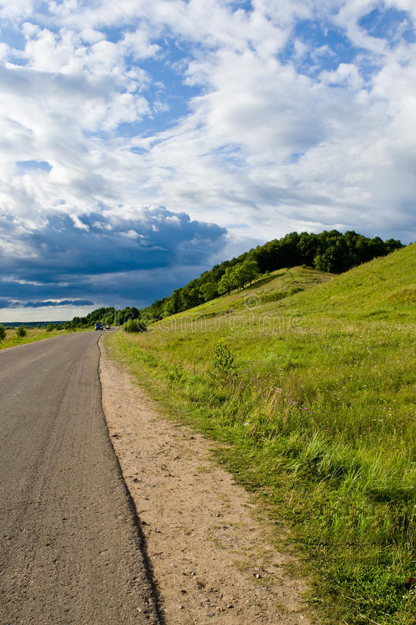 Asphalt road near green grass hill. In summer royalty free stock photography