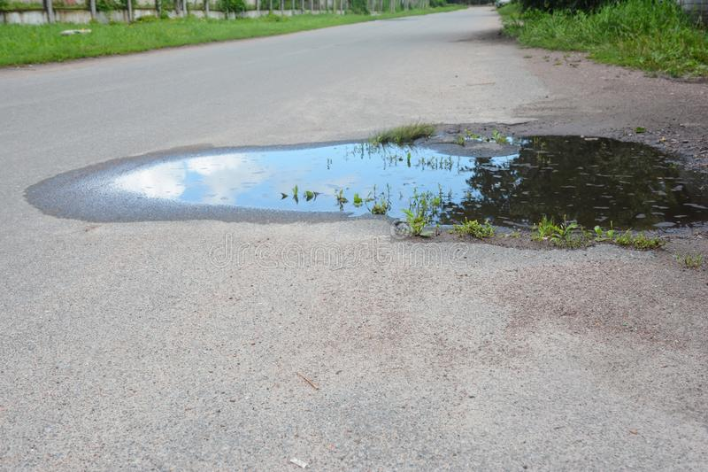 Asphalt road on puddles. Pot hole or pothole image of a broken cracked asphalt pavement royalty free stock photos