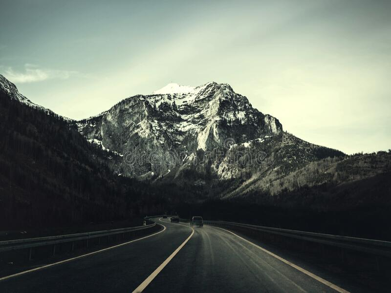 Asphalt Road With Running Vehicle Infront of Mountain Under Gray Sky royalty free stock images