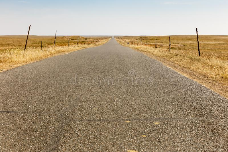 Asphalt road in the steppe with wind generators on the horizon, Inner Mongolia royalty free stock images