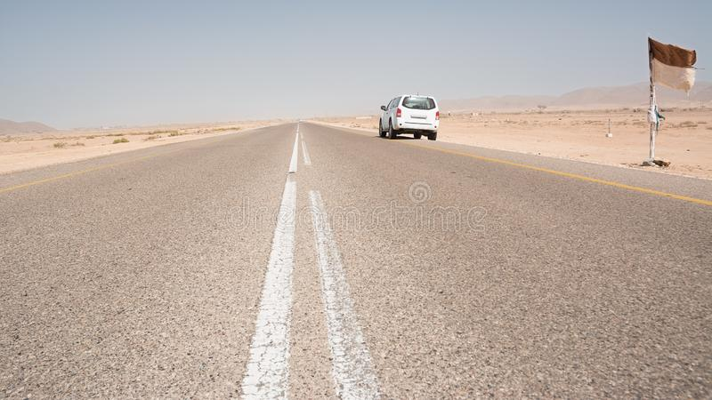 Asphalt road straight in the desert in the south of Oman with a parked 4x4 vehicle stock photos
