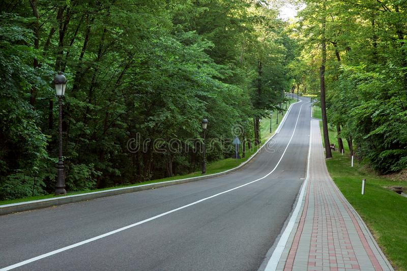 Asphalt road with strip markings down and perspective. Asphalt road with strip markings down and perspective with a turn, forest road with pedestrian pavement stock photo