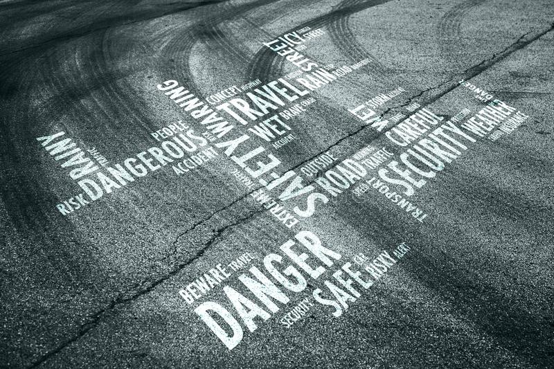 Road with danger word cloud. Asphalt road with tire tracks background and conceptual danger word cloud royalty free stock image