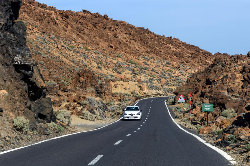 Asphalt road to volcano Teide among rocky mountains on Tenerife island, Spain. TEIDE, TENERIFE, SPAIN - DECEMBER 2015: Asphalt road to volcano Teide among rocky stock image