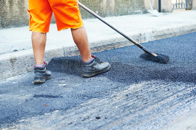 Asphalt road work . Repair urban street. Asphalt road repair work. builder worker repairing street asphalting pavement stock images