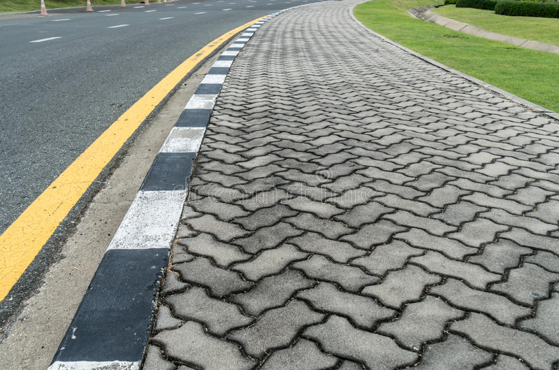 Asphalt road with yellow line. Curve and concrete block sidewalk royalty free stock images