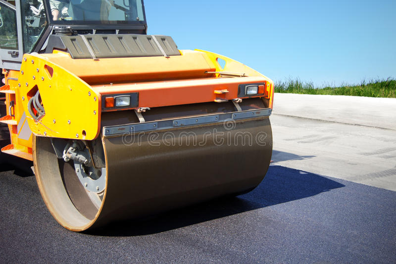 Asphalt roller puts a new road. Asphalt roller at work, construction of new roads, repair of pavement, lining country roads, modern construction equipment stock photography