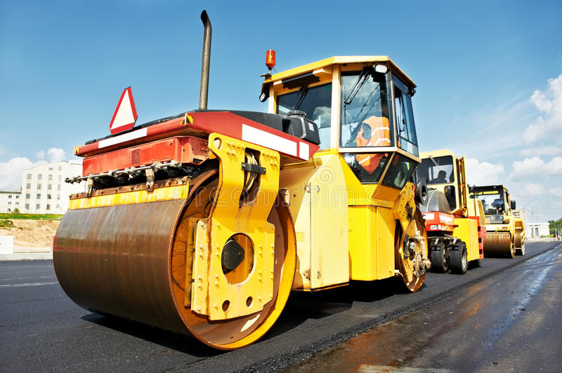 Asphalt roller at work. Heavy tandem Vibration roller compactor at asphalt pavement works for road repairing stock images