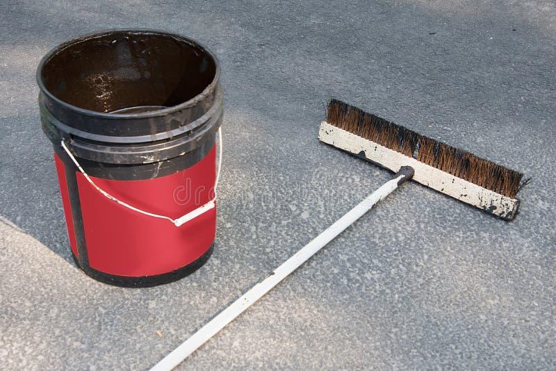 Asphalt sealer and brush. Used driveway sealing brush with bucket of asphalt sealer on unsealed driveway royalty free stock photo