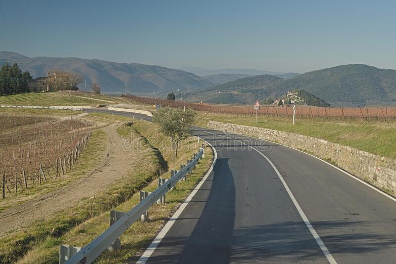 Asphalted provincial road crosses the hills of Tuscany. Cross the hills of Tuscany on a small provincial road on a beautiful sunny winter day with intense and royalty free stock image