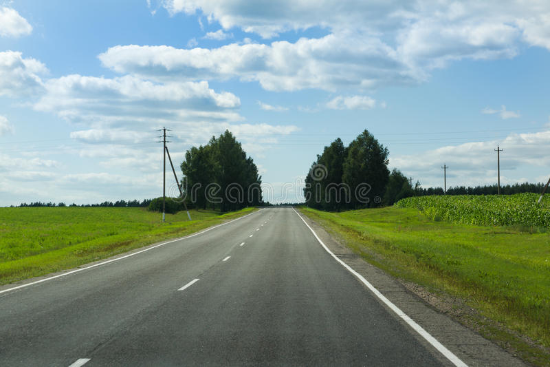 The asphalted way paved along fields royalty free stock images