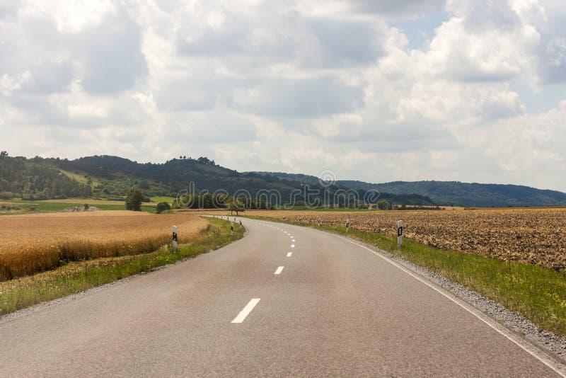 Asphaltez la route rurale de pays en Allemagne par le champ vert image stock