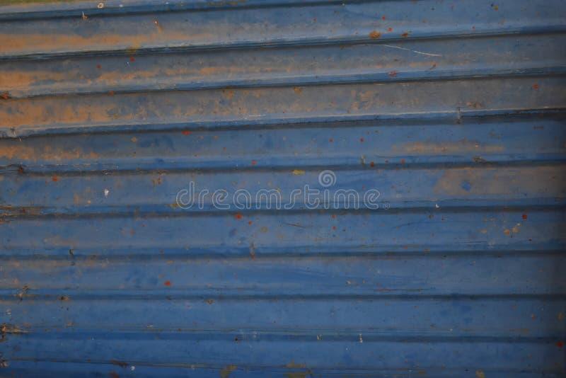 Asphaltieren Sie alte blaue Stahltür des Hintergrundes und schmutzigen Fensterladen der abstrakten Beschaffenheit stockfotografie