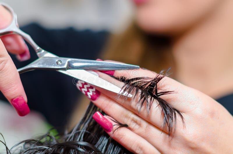 Asphaltieren Sie die Scheren, die einem Herrenfriseur helfen, einen netten Haarschnitt, Abschluss zu bilden lizenzfreie stockfotos