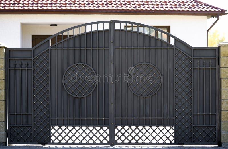 Asphaltieren Sie doppelte Tore für Eintritt von Autos in das Yard geschlossen stockfotografie