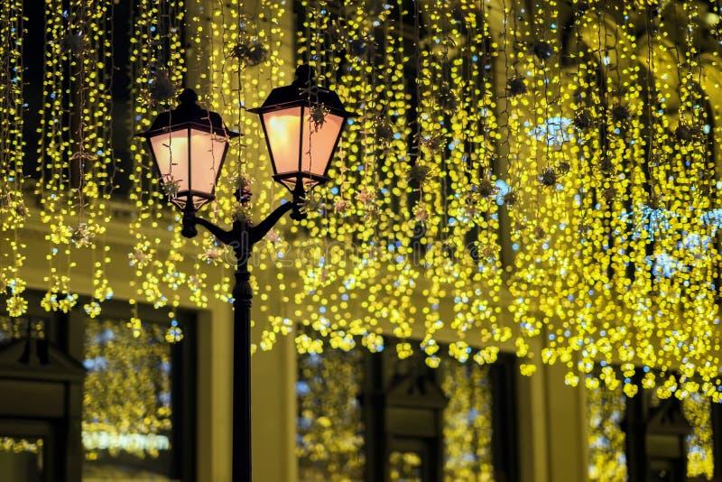 Asphaltieren Sie Laterne auf Hintergrund der glänzenden Neongirlande, wie gelb gefärbte Blätter, Weinlese tont Fall, Festhintergr lizenzfreie stockbilder