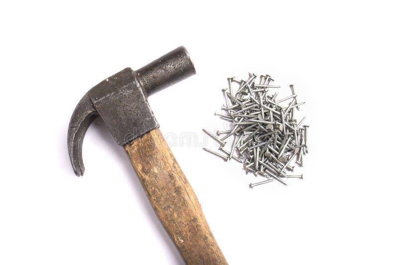 Asphaltieren Sie Nägel und einen Hammer, der auf einem weißen Hintergrund lokalisiert wird lizenzfreie stockfotos
