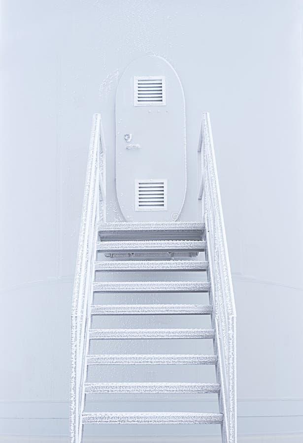 Asphaltieren Sie Treppe zu einer kleinen ovalen Tür, die im Frost bedeckt wird stockfotografie