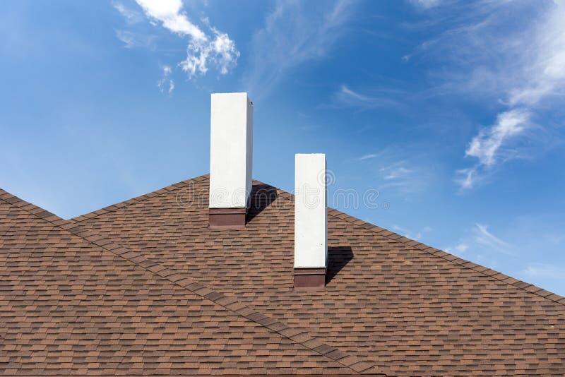 Asphaltieren Sie Ziegeldach mit Kamin auf neuem Haus im Bau lizenzfreie stockfotos