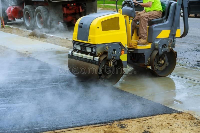 Asphalting construction works with commercial repair equipment road crews royalty free stock photo