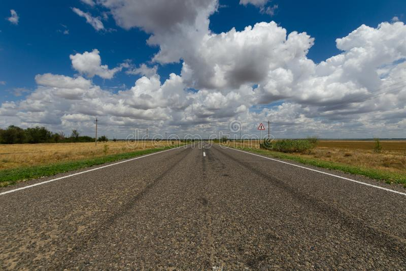 Asphaltstraße in der Steppe und in den Wolken im blauen Himmel lizenzfreie stockfotografie