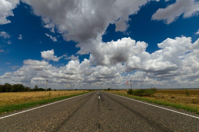 Asphaltstraße in der Steppe und in den Wolken im blauen Himmel lizenzfreie stockbilder
