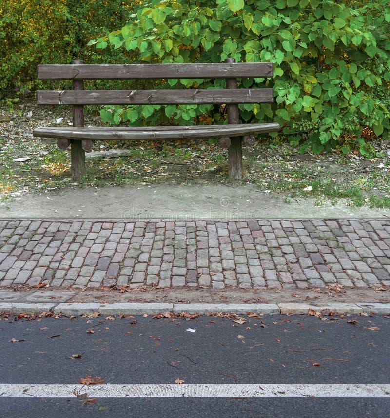 Asphhalt sid vägen, och parkerar gamla trä för kubsten bänken arkivfoto