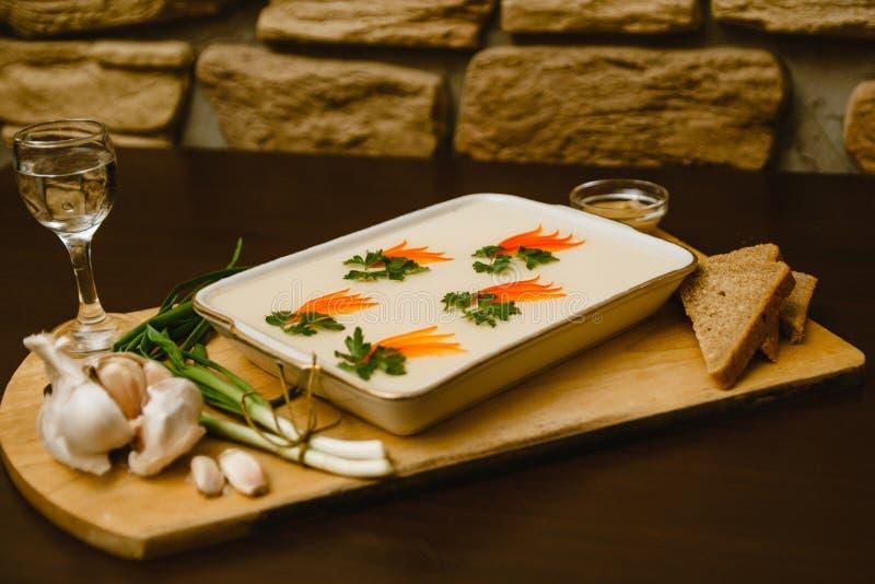Aspic, décoré des carottes, persil sur un fond en bois nourriture Russe-nationale avec alcool illégal, vodka, ail, oignons verts image libre de droits