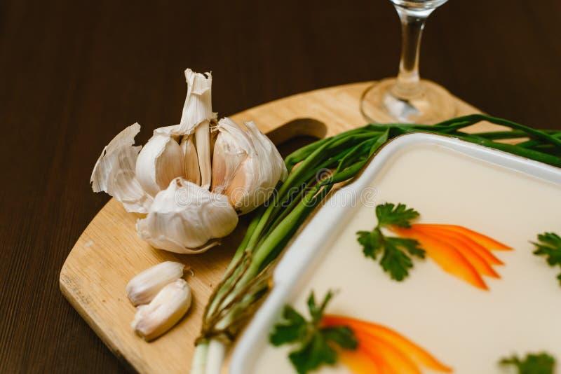 Aspic, décoré des carottes, persil sur un fond en bois nourriture Russe-nationale avec alcool illégal, vodka, ail, oignons verts photo libre de droits