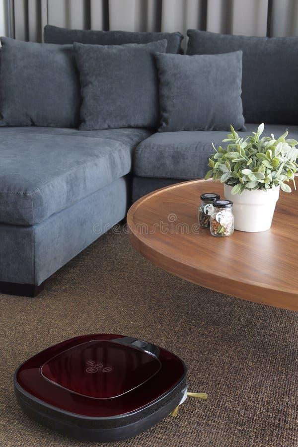 Aspirador del robot que limpia el piso en sala de estar fotografía de archivo
